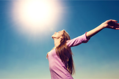 woman spread her hands at the heat of the sun